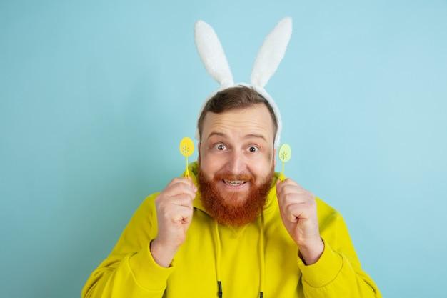 Homme de race blanche avec un décor traditionnel comme un lapin de pâques avec des vêtements décontractés lumineux sur fond bleu studio. bonnes salutations de pâques. concept d'émotions humaines, expression faciale, vacances. copyspace.