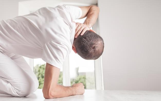 Un homme de race blanche fait un massage de la tête.