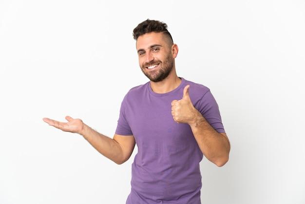 Homme de race blanche isolé sur fond blanc tenant un espace de copie imaginaire sur la paume pour insérer une annonce et avec les pouces vers le haut
