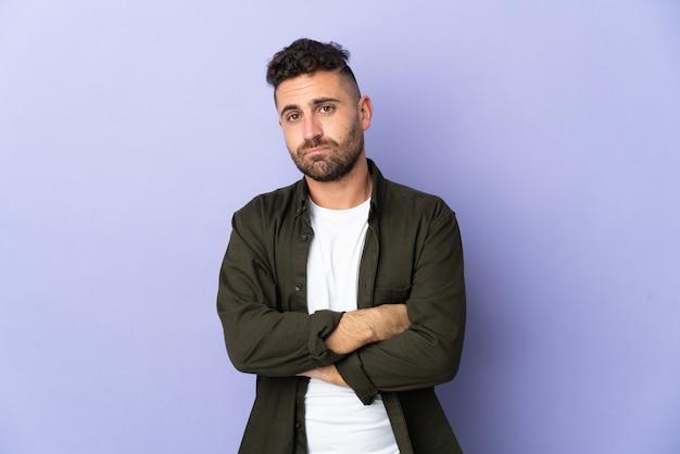 Homme de race blanche isolé sur un mur violet avec une expression triste