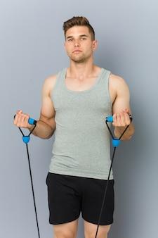 Homme de race blanche jeune fitness pratiquant avec un élastique.