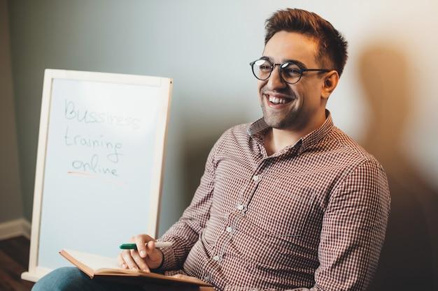 Homme de race blanche avec des lunettes parle et sourit tout en ayant des cours de commerce en ligne
