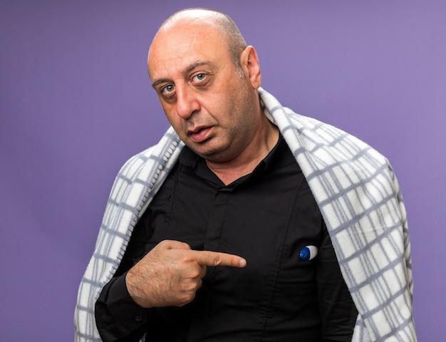 Homme de race blanche malade adulte confiant enveloppé dans la mesure de la température plaid et pointant sur thermomètre isolé sur mur violet avec espace copie