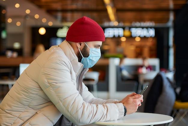 Un homme de race blanche avec un masque chirurgical sur le visage à l'aide d'un smartphone dans le centre commercial.