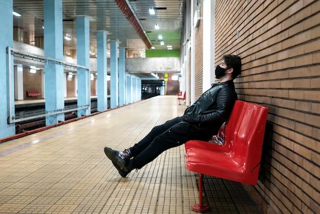 Un homme de race blanche en masque médical noir assis sur une chaise dans le métro