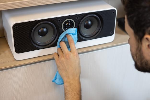 Un homme de race blanche méconnaissable fait un nettoyage humide, époussetant un système de haut-parleurs musicaux. concept de nettoyage de printemps, hygiène dans la maison, changement de rôle dans la famille. mise au point sélective douce.