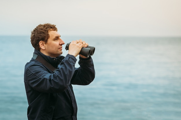 Homme de race blanche sur la mer prêt à regarder à travers des jumelles