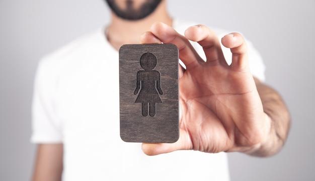 Homme de race blanche montrant le symbole féminin en bois.