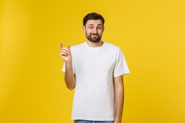Un homme de race blanche montre une petite taille par les doigts démontre une petite mesure, parle de peu de prix réduits studio shot mur jaune