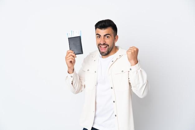 Homme de race blanche sur mur blanc isolé heureux en vacances avec passeport et billets d'avion