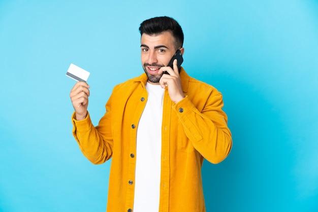 Homme de race blanche sur mur bleu isolé en gardant une conversation avec le téléphone mobile et tenant une carte de crédit