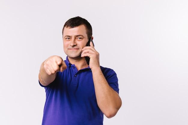 Homme de race blanche parlant sur un téléphone portable et montre son index à la caméra. fond blanc et