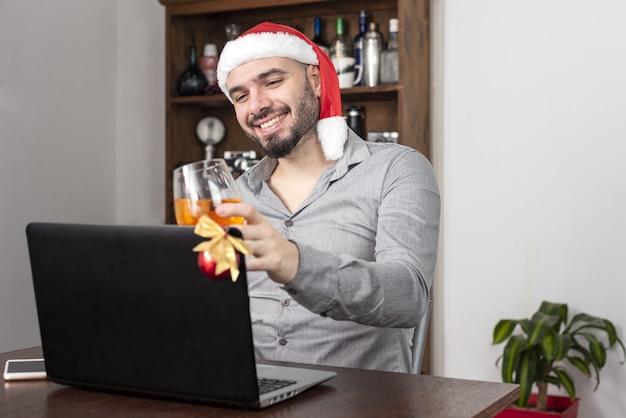 Homme de race blanche portant un chapeau de père noël buvant un toast lors d'une réunion en ligne