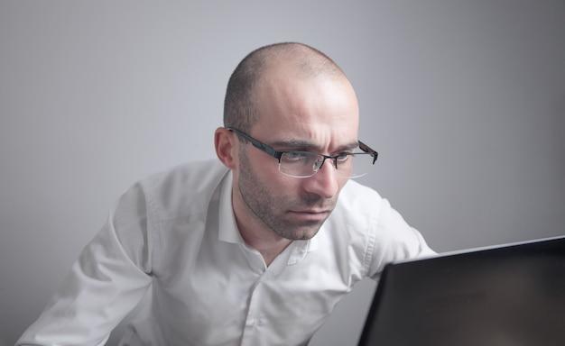 Homme de race blanche portant des lunettes travaillant avec un ordinateur portable.