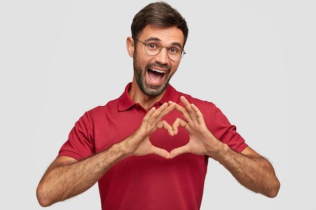 Homme de race blanche positive avec une expression heureuse, montre le geste du cœur sur la poitrine, exprime une attitude amicale et de l'amour, porte un t-shirt rouge vif, isolé sur un mur blanc