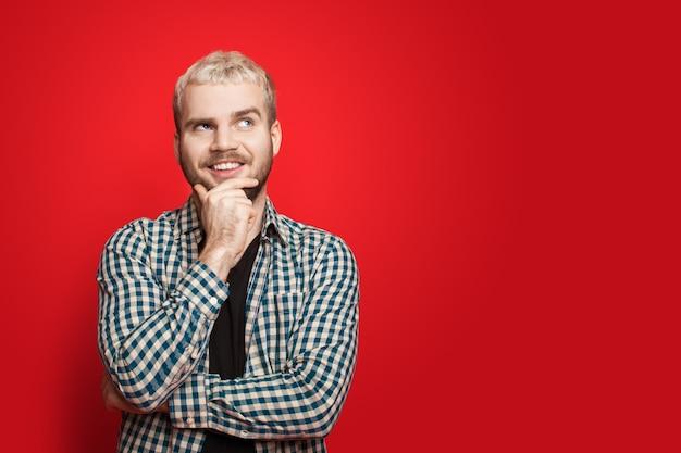 Homme de race blanche qui a eu l'idée et pose de côté sur un mur rouge avec un espace libre touchant son menton et son sourire