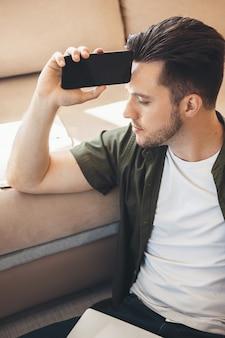 Homme de race blanche réfléchie avec barbe tenant un téléphone et un ordinateur portable sur le sol en pensant à quelque chose
