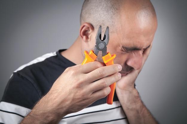 Homme de race blanche souffrant de maux de dents tenant une pince.