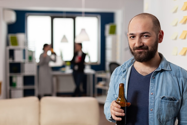 Homme de race blanche souriant et tenant une bouteille de bière après le travail à la fête de bureau. collègues réunis pour des activités amusantes tout en jouant à des jeux en mangeant de l'alcool. boissons de célébration