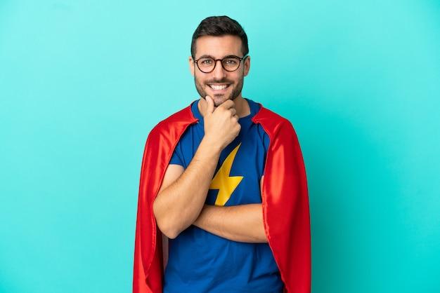 Homme de race blanche de super héros isolé sur fond bleu avec des lunettes et souriant