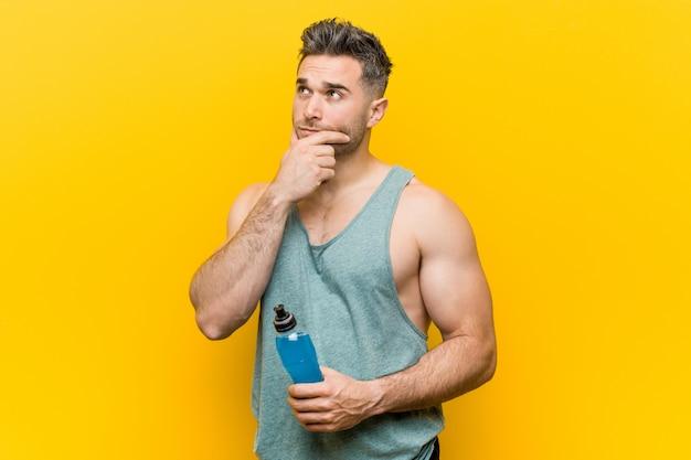 Homme de race blanche tenant une boisson énergisante à côté avec une expression douteuse et sceptique.