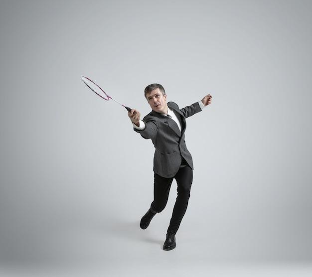 Homme de race blanche en tenue de bureau joue au badminton isolé sur mur gris
