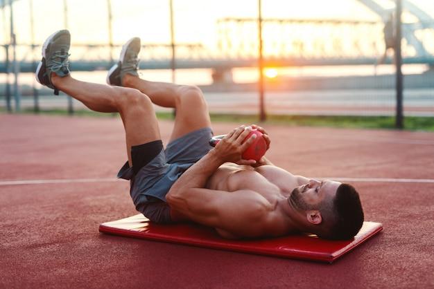 Homme de race blanche torse nu musclé avec une expression faciale sérieuse, faire des exercices avec kettlebell en position couchée sur le tapis sur le court le matin.