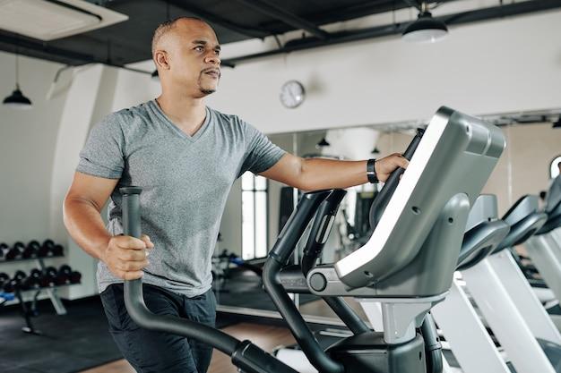 Homme de race mixte mature sérieux travaillant sur machine elliptique dans une salle de sport pour se réchauffer avant l'entraînement