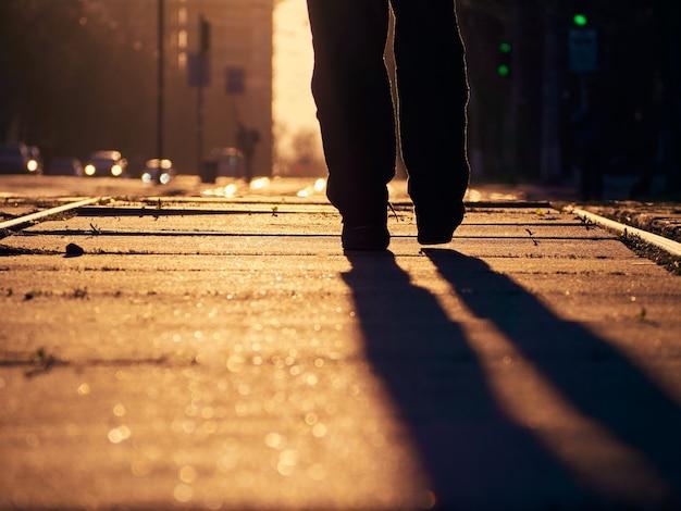 Homme sur les rails au coucher du soleil.