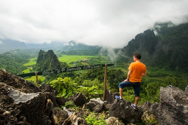 Homme de randonnée se tenir au sommet de la montagne avec vue sur la nature.
