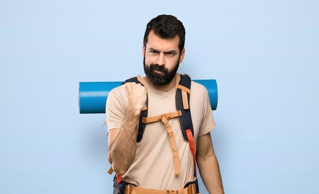 Homme de randonneur avec geste en colère sur fond bleu isolé