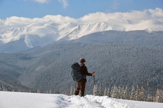 Homme randonneur randonnée à flanc de montagne enneigée par une froide journée d'hiver.