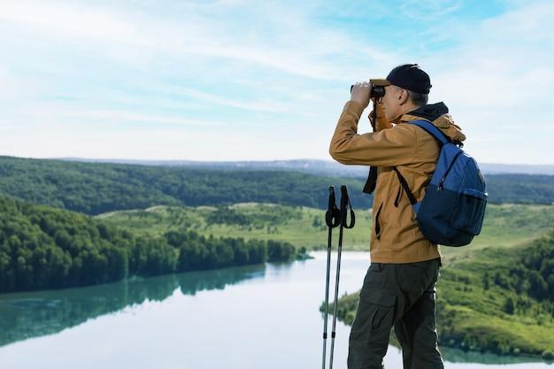 Homme de randonneur regardant dans des jumelles sur la montagne. randonnée mode de vie des personnes actives.