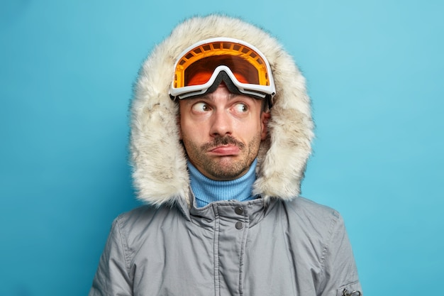 Homme randonneur regarde pensivement de côté porte des lunettes de ski et une veste d'hiver avec capuche a un repos actif pendant les vacances aime le sport préféré.