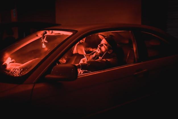 Homme rappeur dans une casquette dans une voiture qui fume la nuit dans un garage éclairé par un feu rouge en hiver, voiture de sport