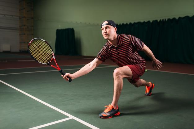 Homme avec raquette de tennis jouant sur un court intérieur. entraînement sportif du joueur de tennis masculin