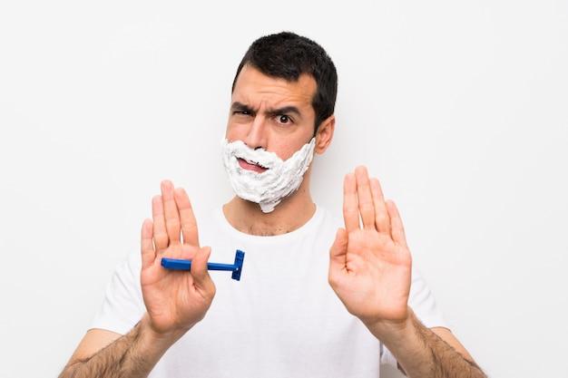 Homme rasant sa barbe sur un mur blanc isolé, arrêtant le geste et déçu