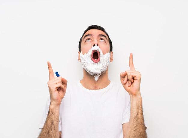 Homme rasant sa barbe sur un mur blanc isolé surpris et pointant vers le haut