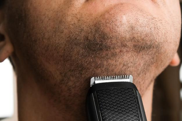 Homme rasant sa courte chaume. irritation après le concept de rasage au rasoir électrique.