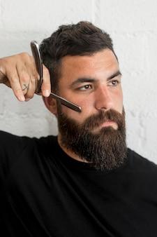 Homme avec rasoir en studio
