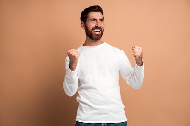 Homme ravi extrêmement excité avec une barbe faisant un geste oui, émerveillé par sa victoire, triomphe. studio intérieur tourné isolé sur fond beige