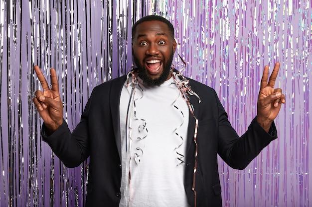 Un homme ravi à la peau sombre lève les mains, montre un geste de paix, rit joyeusement, a de la serpentine sur le corps, vêtu d'un costume élégant, exprime des émotions positives, se tient sur un mur violet décoré