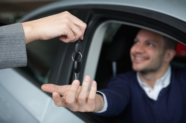 Homme recevant des clés de voiture assis dans sa voiture