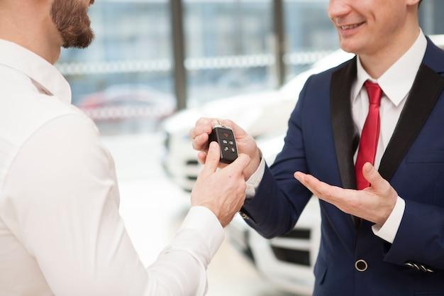 Homme recevant les clés de voiture du vendeur chez le concessionnaire