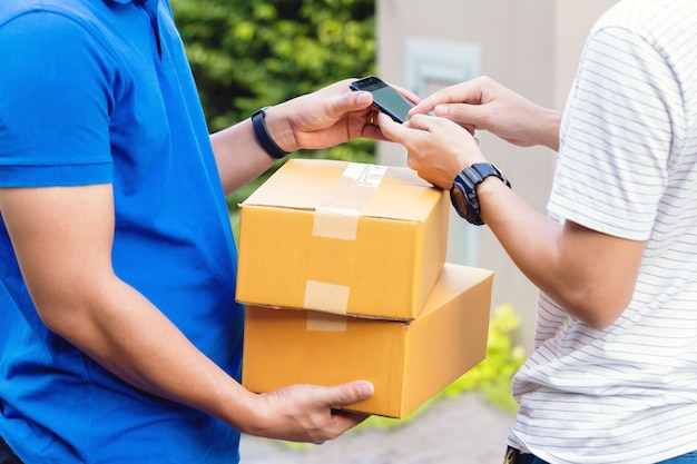 Homme recevant le colis du livreur, apposant sa signature au téléphone numérique après avoir reçu un colis de courrier à la maison.
