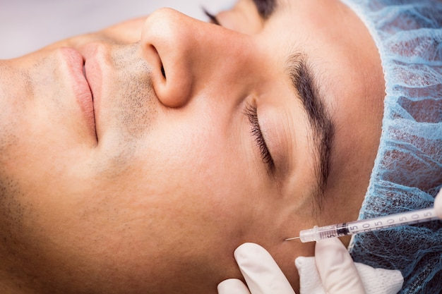 Homme recevant une injection de botox sur son visage