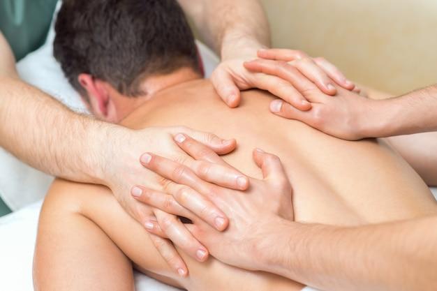 Un homme recevant un massage de bien-être à quatre mains.