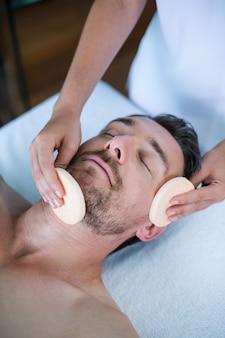 Homme recevant un massage du visage d'un masseur
