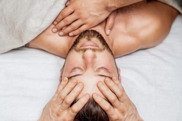 Homme recevant un massage de la tête.