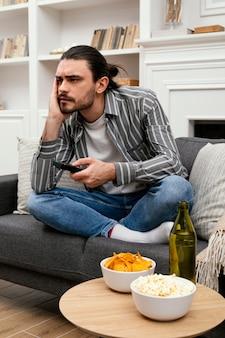 Homme à la recherche d'une chaîne à la télévision